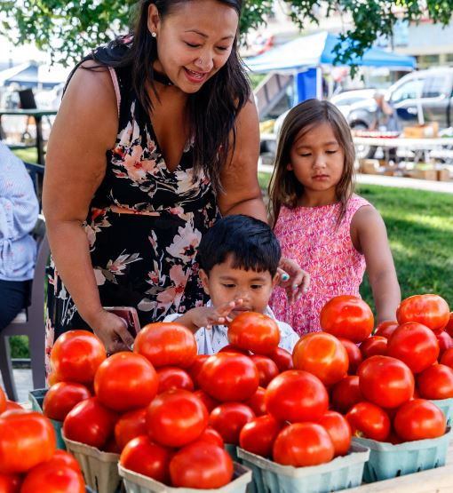 Mom and kids looking at tomatoes at the farmers market